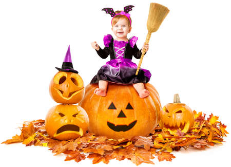 Halloween Happy Little Witch Sitting on Pumpkin in Carnival Costume, Smiling Child Girl Holding Broom and Candy, Witchcraft over Isolated White Background