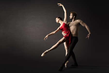 Ballet Dancers. Modern Ballerina Couple Posing over Gray Background