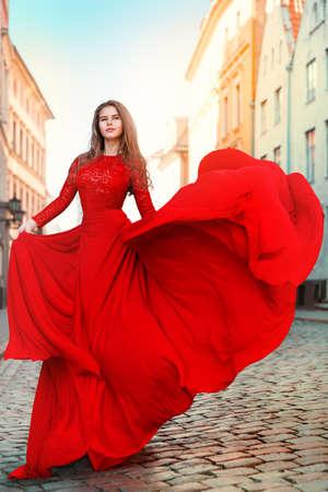 Beautiful Woman in Waving Long Fluttering Red Dress Walking on the City Street. Outdoor Brunette Portrait in Sun