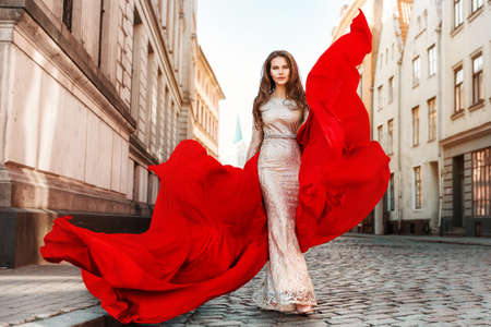 Fashion Model in Evening Dress with Flying Red Fabric. Woman Walking in City. Outdoor Urban Glamour Full Length Portrait