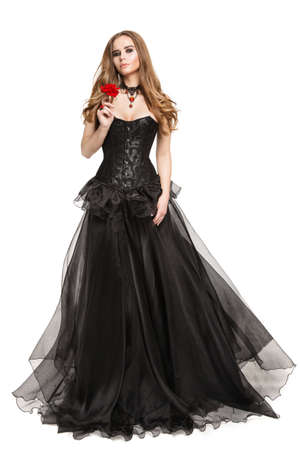 Fashion Model in Black Corset Retro Dress smelling Red Rose Flower, Full Length Beautiful Woman Portrait in Evening Gown on Isolated White