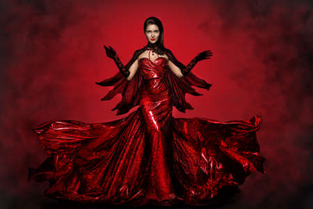 Beautiful Halloween Witch in Red Dress, Gloves and Cape, Gothic Fashion Girl Raised Open Arms, making Magic Witchcraft. Spooky Dark Smoke Background