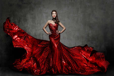 Woman Red Dress, Fashion Model in Long Silk Gown Waving Cloth on Wind, Flying Fluttering Fabric over Gray Background
