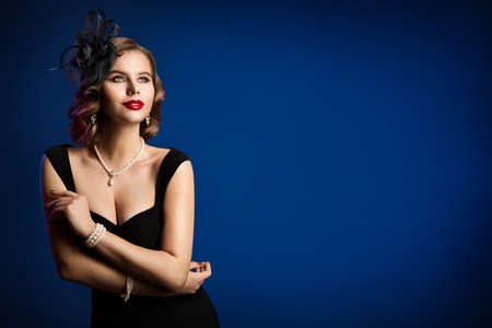 Retro Fashion Model in Black dress and Hat, Old Fashioned Woman Portrait, Luxury Style Hair Makeup Jewelry over Blue Background Banco de Imagens