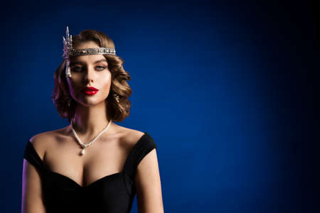 Retro Beautiful Flapper Woman, Vintage Wave Hairstyle, Makeup, Red Lips, Glamour Model Old Fashioned Portrait over Blue Background