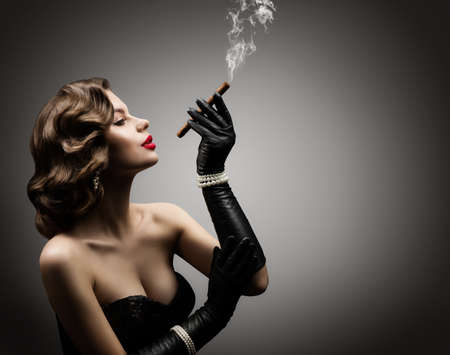 Retro Woman Smoking Cigar, in Corset and Gloves, Beautiful Old Fashioned Model Portrait over Gray Studio Background, Side View Banco de Imagens