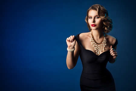 Retro Fashion Model, Old Fashioned Woman Beauty Portrait in Black Dress, Hairstyle Makeup Luxury Jewelry over Blue Background Banco de Imagens