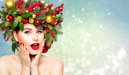 Christmas Woman Beauty in Xmas Wreath. New Year Fashion Model Happy Laughing, Open Mouth. Emotional Face, Red Lipstick over Snow Background