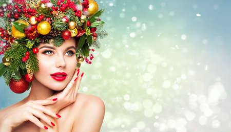 Christmas Woman Beauty Makeup, Xmas Wreath Hairstyle. Winter Fashion Model Portrait with Red Lips Make up, Beautiful Girl on Blue Snowy Background