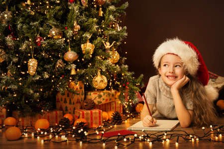 Christmas Kid Write Letter to Santa Claus. Child in Christmas Hat wishing New Year Gift on Xmas Eve in Holiday Room with Christmas Tree Banco de Imagens