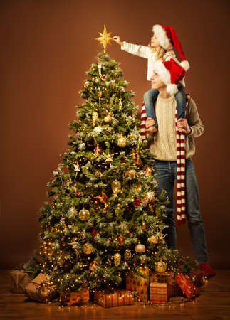 Christmas Family Decorate Xmas Tree. Child in Santa Hat putting Star on Top. Happy Father Together with Daughter indoors Portrait. Christmas tree Lights and Baubles in Dark Banco de Imagens