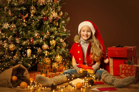Christmas Child Santa Helper Packing Gifts. Happy Elf Girl Reading Xmas Letters. Decorated Christmas tree and Stack of New Year Presents.