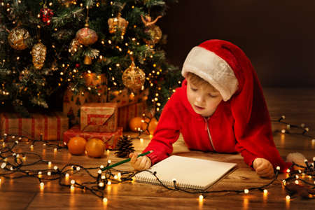 Christmas Child Write Letter to Santa Letter. Kid in Xmas Hat Writing Gift Wish List next to Christmas Tree over dark Background