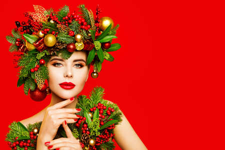 Christmas Woman Beauty Makeup, Wreath Hairstyle. Fashion Model Xmas Portrait, Beautiful Girl with New Year Decoration Hair on Red Background
