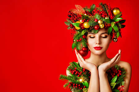 Christmas Face and Hands Skin Winter Care, Woman Makeup, Art Xmas Tree Wreath Hairstyle,  Beautiful Portrait, Model looking to Product on Hand over Red