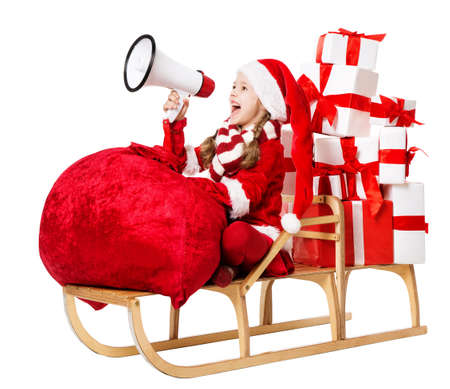 Christmas Child screaming Megaphone, delivering Xmas Gifts, Huge Bag full with Presents. Little Girl Elf in Santa Hat riding Sleigh over White Cut out Background