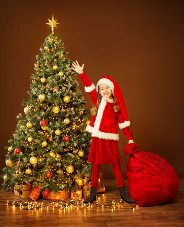 Christmas Happy Child in Elf Costume Holding Red Santa Bag with New Year Gifts under Xmas tree. Decorate Illuminated Home Room