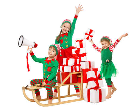 Funny Christmas Kids with Megaphone preparing New Year Gifts. Santa Claus Helpers, Cute Little Elves on Sleigh packing Christmas Present Boxes in Stack