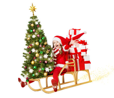 Little Santa Girl with Christmas tree and Stack of New Year Gifts. Happy Child in Santa Hat riding fast on Sleight. Express Delivery and Holiday Sale Shopping Concept. Isolated White Banco de Imagens