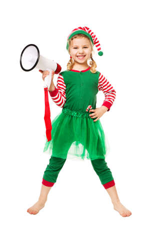 Adorable Little Christmas Elf Girl holding Megaphone.  Happy Smiling Child in Masquerade Costume. Christmas Advert and Sale Concept. Isolated White Background