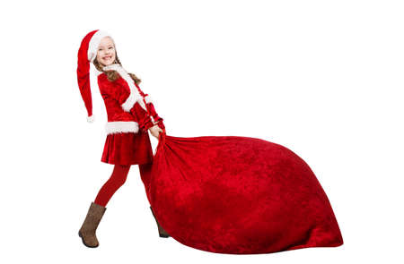 Little Santa Claus Girl Pulling Huge Red Christmas Bag Full of Gifts.  Funny Child in Santa Hat and Costume Carrying Big Sack with New Year Presents. Isolated White Banco de Imagens