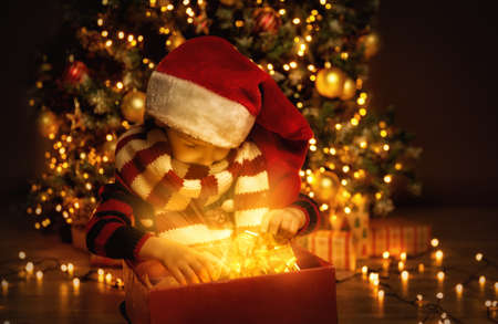 Christmas Child Opening New Year Present, Happy Baby Boy looking to Magic Light in Gift Box, Kid in front of decorated Xmas Tree Interior