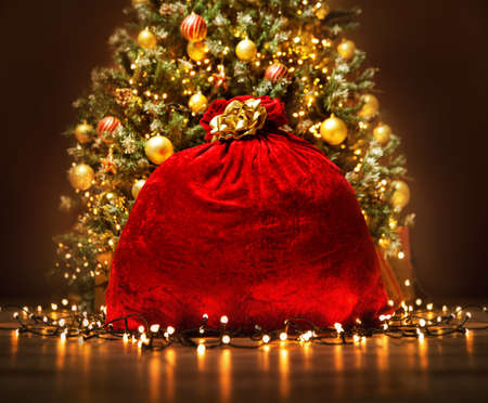 Santa Claus Red Bag full with Toy Gifts, Christmas Presents. Christmas Sack tied by Golden Bow Ribbon over Decorated lightening Christmas Tree in dark Room