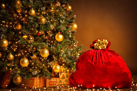 Santa Red Bag full with Gifts. Christmas tree Decorated by Golden Balls and Present Box under. Xmas Sack tied by Golden Ribbon over Brown Background Banco de Imagens