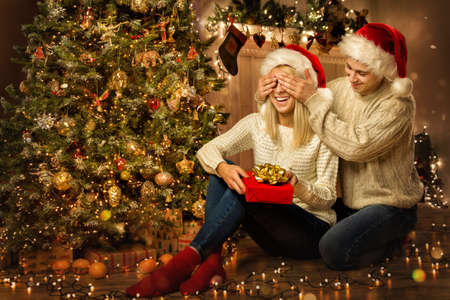 Christmas Family Couple with Gift. Man giving Present to surprised Woman next to Xmas tree. Closing eyes to Girlfriend in Room Decorated with Lights Banco de Imagens