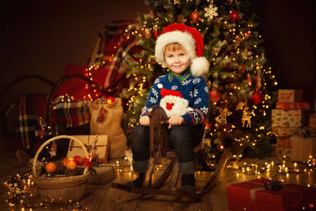 Little Cute Boy in Christmas Decorated Room Interior. Child on vintage wooden Toy Horse. Christmas tree with rustic ornament shining in Dark Night Banco de Imagens
