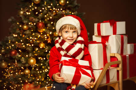Happy Child in Santa Hat holding Gift. Stack of Xmas Presents on Christmas tree Lights Background