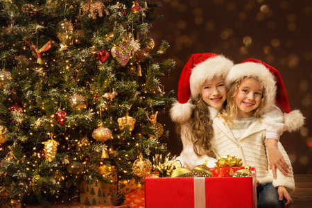 Christmas Children Sisters opening Present Box with Gift Toys. Happy smiling little Girls in Santa Hat near to Christmas tree in dark background
