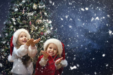 Christmas funny Kids catching Snow in Hands. Happy Children on Winter Holiday Vacation playing outside. Snowfall. Xmas Eve Night