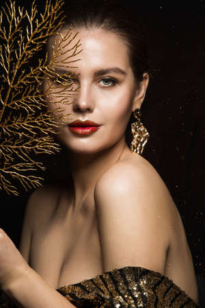 Luxury Woman Portrait with Gold Jewelry. Mystery Girl hiding Face. Glitter Make up. Elegant Lady over Black Background