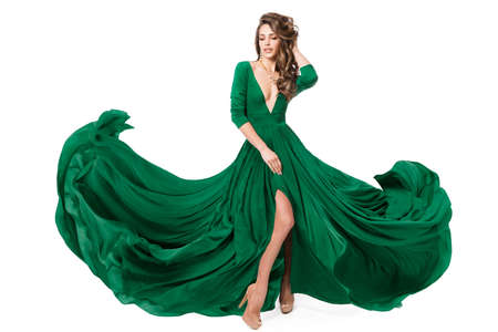 Woman Green Fashion Dress. Model in Long Evening Slit Gown waving on Wind. Fashionable Beauty Girl dancing on Isolated White Background