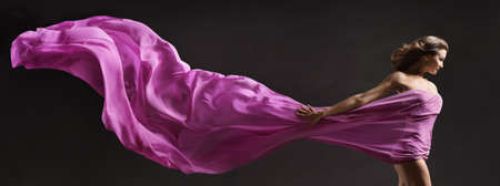 Woman dancing. Modern Ballet Dancer with long Fabric Banner flying on Wind in Air. Copy Space. Black Background Foto de archivo