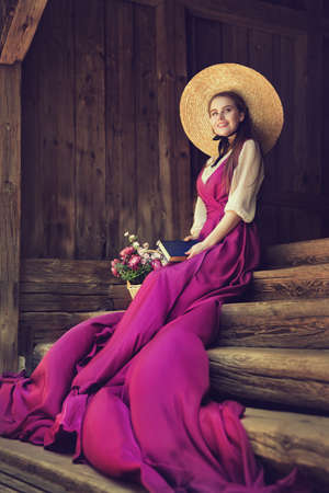 Romantic Vintage Woman in Summer Hat dreaming with Book on wooden Stairs Background. Victorian Fashion Portrait