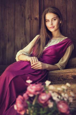 Vintage Woman Portrait blossom Flower in Basket. Beauty Model happy smiling over dark Wooden Background Pink Dress Foto de archivo