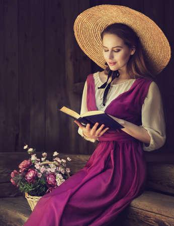 Romantic Vintage Woman reading Book. Women Bible Study over dark Wooden Background. Victorian Era Portrait in Summer Straw Hat Historical Dress Foto de archivo