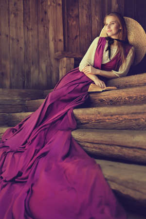 Romantic Vintage Woman Fashion. Victorian Lady relax Outside on wooden Steps. 19th Century Female Historical Dress Costume