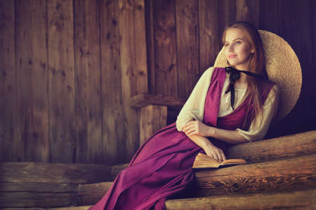 Victorian Woman Portrait. Dreaming Country Side Romantic Beauty Girl over dark wooden Background Copy Space. Outside Fashion