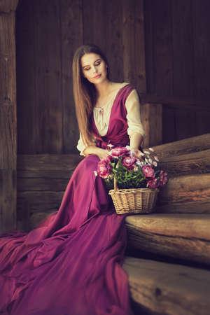 Romantic Woman Flower Bouquet in Basket. Vintage Model in Pink Fashion Dress sitting on wooden Steps