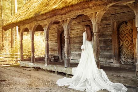 Wedding Bride Dress Rear View Outdoors. Vintage White Bridal Gown over Old Wooden Terrace. Romantic Woman Portrait Foto de archivo