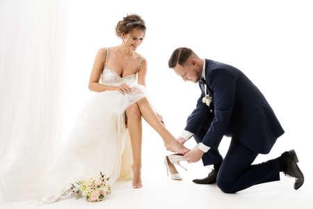 Fashion Wedding Couple. Groom putting on Cinderella Shoes on Bride Leg. Elegant Bridal Preparation. Isolated white