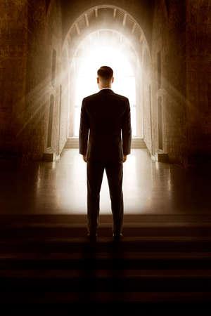 Man Back View Silhouette in Window Door Light.  Groom in Black Suit Standing Dark Mystery Church Aisle