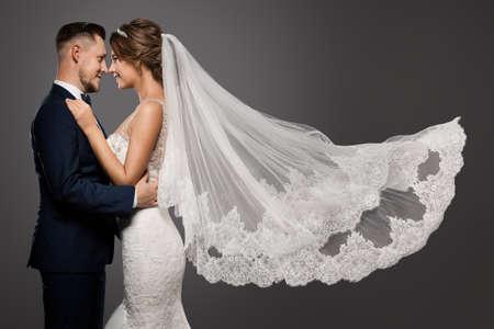 Wedding Couple Dancing. Romantic Bride and Groom Portrait. Bridal long Veil flying over Gray Studio Background