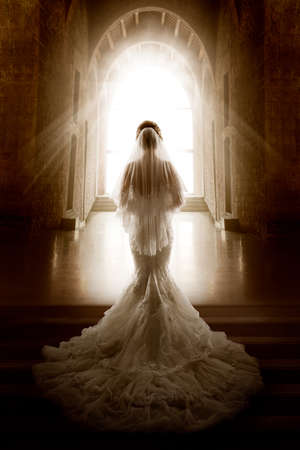 Bride Back Side View walking down Aisle Church. Wedding Ceremony Day. Bridal Dress long Train and Lace Veil. Indoor Art Portrait