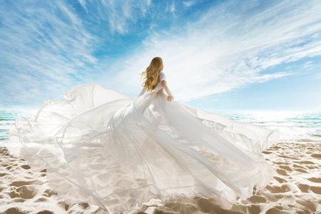 Woman on Beach in White Dress flying on Wind. Summer Vacation. Beach Sand Sea Sunshine Sky
