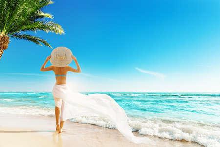 Woman Summer Beach Vacation. Travel Girl Sunbathing in Sun Hat, Bikini, White fluttering Dress. Women Back View looking at Ocean
