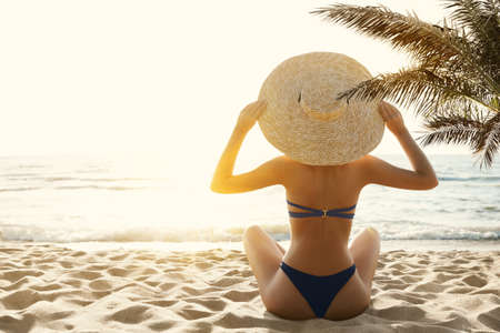 Woman Bikini Tropical Beach Back View. Beauty Model Girl in Sumer Hat Sun Tanning under Palm. Summer Beach Vacation. Holiday Sea Travel